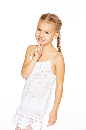 baby girls smiley face: Funny little girl with a charming smile in a white dress showing silence sign