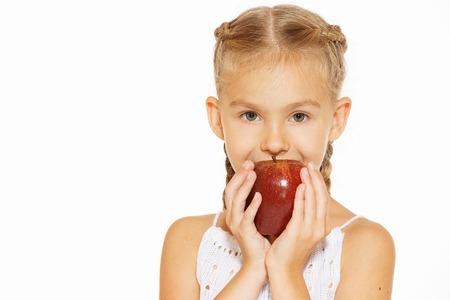 eating fruits: Cute little girl in a white dress bites red fresh apple Stock Photo