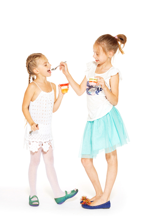 only teenage girls: Beautiful little girls in white dress eating jelly