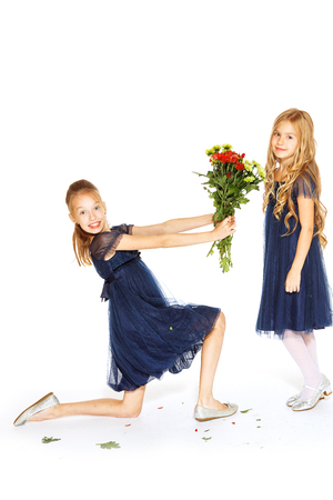green smiley face: Two charming little girls in a blue dresses with a bouquet of flowers Stock Photo