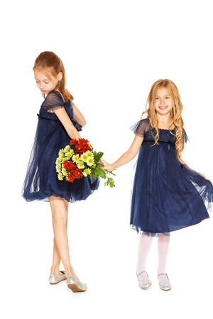 baby girls smiley face: Two charming little girls in a blue dresses with a bouquet of flowers Stock Photo