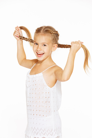 baby girls smiley face: Funny little girl with a charming smile in a white dress holding a pigtails