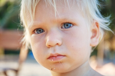 15 18: Baby with blond hair and blue eyes on the beach