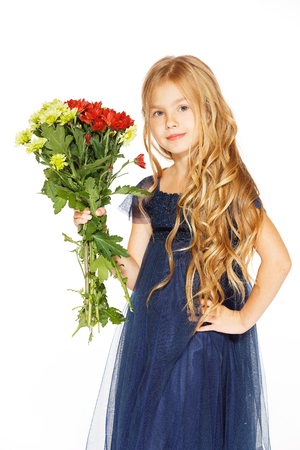 baby girls smiley face: Charming little girl with curly hair in a blue dress with a bouquet of flowers