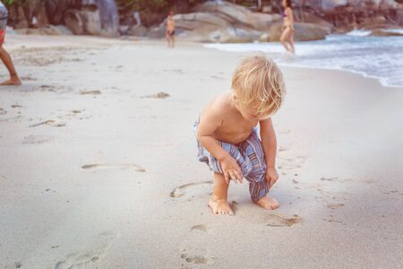 15 18: Toddler in a blue pants walking on a white sand in Thailand