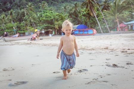15 18: Little boy walking barefoot on white sand beach