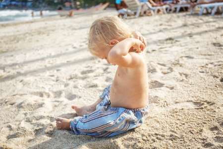 15 18: Baby with blond hair on the white sand beach