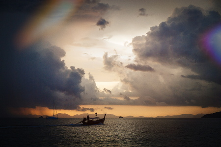 getting away from it all: Boat at sunset on a calm sea in Thailand