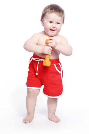 build in: The cheerful smiling kid in red shorts with dumbbells in hands