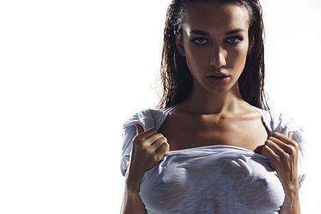 젖은 티셔츠에있는 섹시한 화려한 젊은 여자가 백인에 고립 된