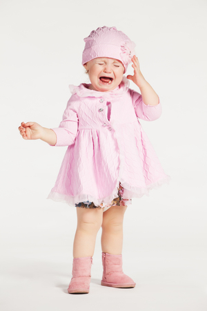 pink dress: Little crying girl in a pink dress on white background Stock Photo