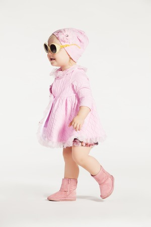 pink dress: Little girl in a pink dress and sunglasses on white background