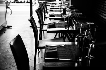 arranging chairs: Table setting in restaurant with wine and water glasses