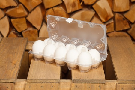 dozen: Dozen of white eggs on brown wooden stand