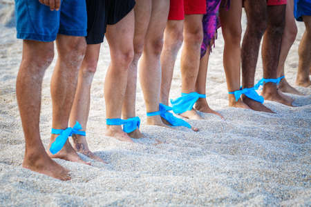 nationalities: Group of people of different nationalities on the sand with legs connected by ribbon