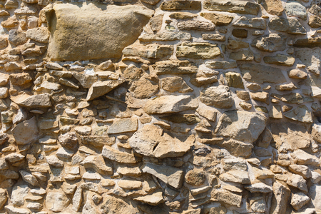 sandy brown: Background rough sandy brown stone wall on a sunny day