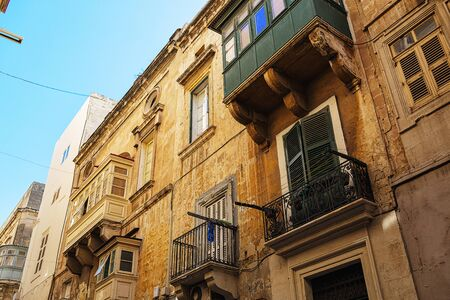 townhouses: Balconies in Malta on the stone facade of historical townhouses