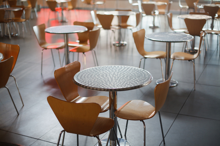 Cafe in airport with brown round tables Imagens