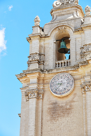 Old bell tower with clock under blue sky