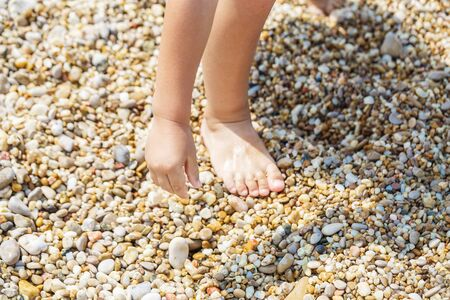 Child hands collect pebbles