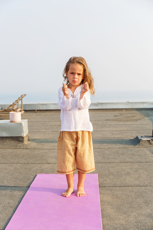 Baby doing yoga on the roof Stock Photo