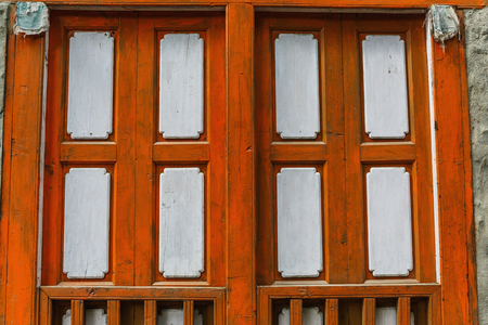 Old textured wooden brown shutters on the stone wall Stock Photo