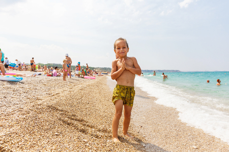 Sweet little boy with hands in namaste on the beach Stock Photo