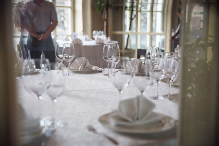Tables set for an event party or wedding reception. Glasses and dishes.