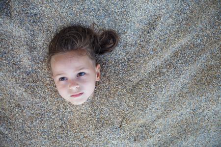 Boy hidden in the sand on the beach
