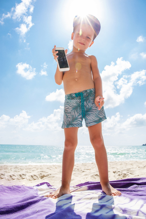 Cute boy is playing in a  mobile phone on the beach