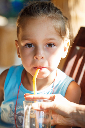 boy is drinking  juice through a tube