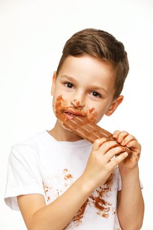 little messy boy is eating chocolate studio shot Stock Photo