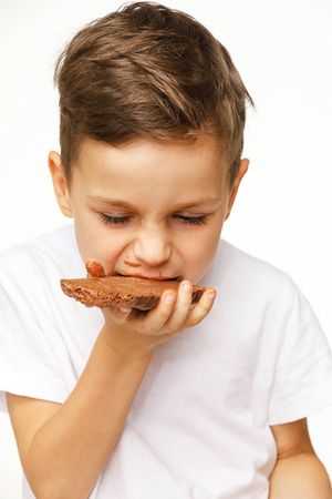 little beautiful boy eating chocolate studio shot