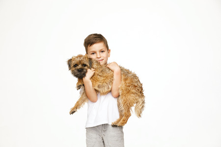 little boy is hugging the dog studio shot