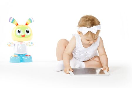 little girl all in white with tablet and toy