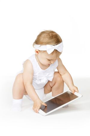 little girl all in white with a tablet
