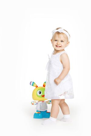 beautiful little girl all in white clothes with a toy Archivio Fotografico