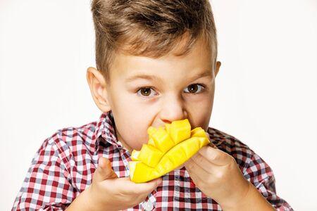 chico guapo con una camisa roja está comiendo un mango