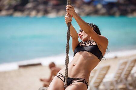 beautiful woman in a black swimsuit on a beach swing