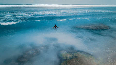 Young woman in a bikini at the white sand near the waves of blue sea. Bali, Indonesia. Aerial Shooting. Stunning tropical beach view. Top view aerial photo from flying drone of an amazingly beautiful