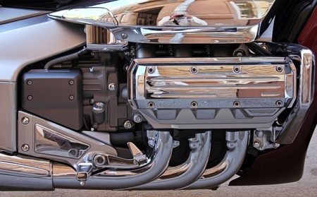 A closeup detailed view of chrome exhaust pipes and engine components on a big chopper bike. photo