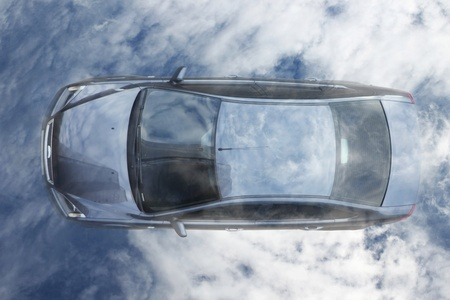 Blue family car against cloudy sky. View from above. photo
