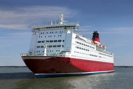 Red and white passenger ship not far from coastline. photo