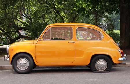 Side view of old small yellow car with flat tire. Editorial