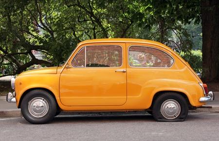 Vue latérale de la vieille voiture jaune avec un pneu crevé.