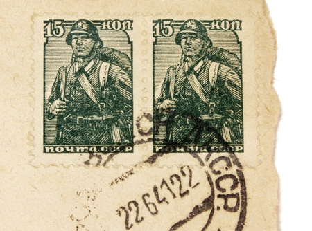 Russia - CIRCA 1941. Two vintage stamps printed in USSR shows image of Russian soldier. Vintage postmark from Soviet Union on an old  envelope (dated 22.06.1941 - first day of the war in Russia) photo
