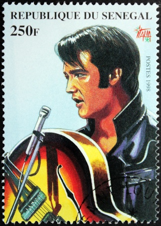 SENEGAL - CIRCA 1998. A postage stamp printed by Senegal shows image portrait of famous American singer Elvis Presley (1935-1977), circa 1998. Stock Photo - 14500515