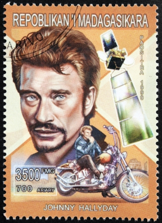 MADAGASCAR - CIRCA 1999: A postage stamp printed by Madagascar shows image portrait of famous French singer and actor Johnny Hallyday (Jean-Philippe Smet), circa 1999. Stock Photo - 14857665