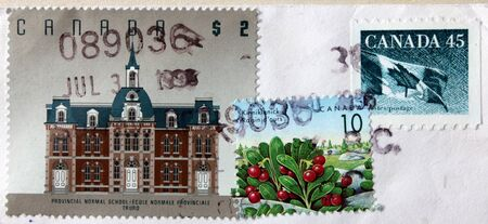 normal school: CANADA - CIRCA 1993  A set of three postage stamps printed by CANADA shows National flag, building of provincial normal school and Canadian berries, circa 1993  Stock Photo