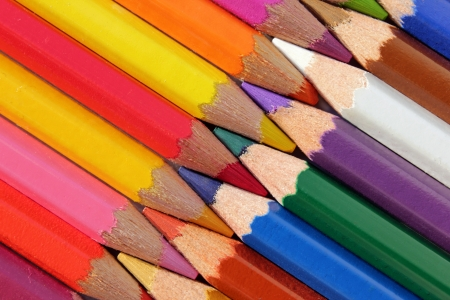 Closeup view of interlaced wooden color pencils against black background. photo